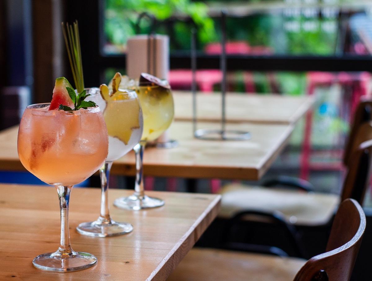 3 pahare de cocktail pe o masa la terasa, in pahare rotunde, ornate cu fructe