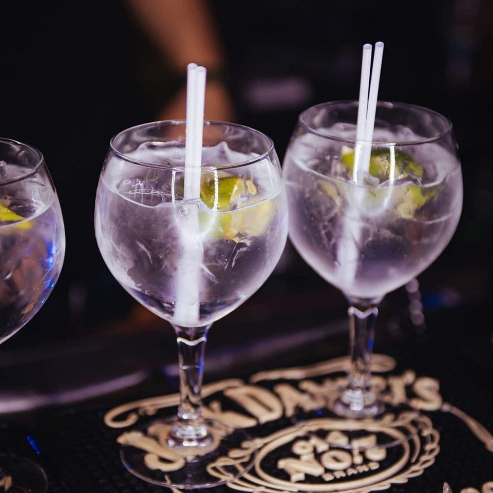 3 pahare de cocktailuri incolore, cu paie, pe fundal negru, la Freddo Bar Lounge, cocktail bar București