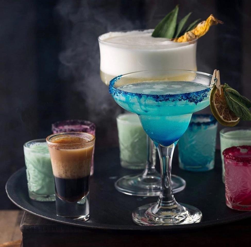 mai multe pahare de cocktail si shoturi, unul albastru si unul alb, de la Ganesha Caffe cocktail bars bucurești