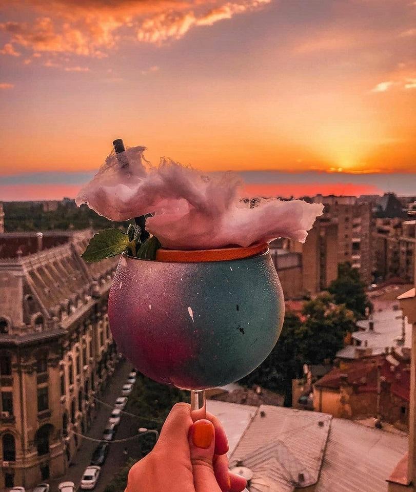 pahar de cocktaul cu vata de zahar, cu apusul de soare in fundal, la Linea Closer to the Moon București