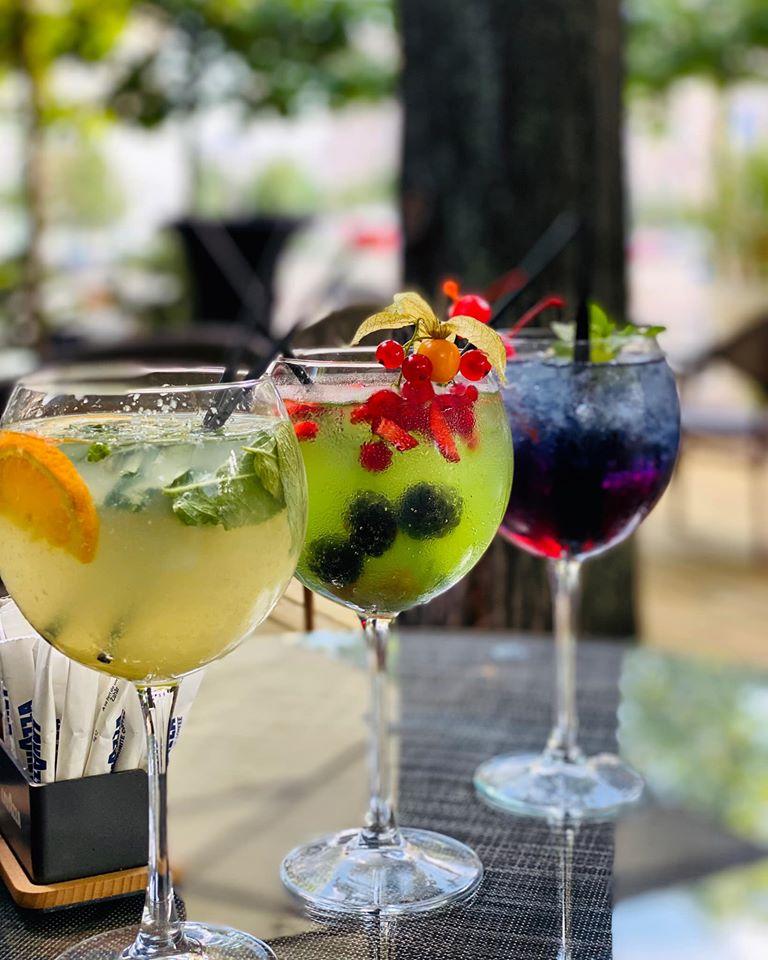 trei pahare de cocktail de culori diferite, ornate cu fructe, de la cocktail bar Colonial Lounge din București