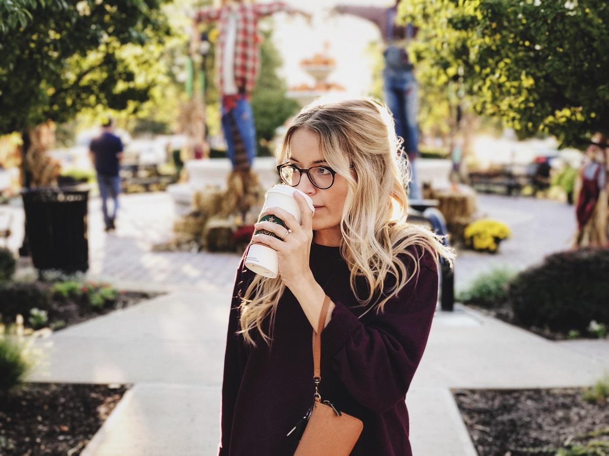 femeie blondă cu păr lung și ochelari, band cafea dintr-un pahar de carton, in oras. imagine reprezentiva pentru cum iti afectează cafeaua sănătatea