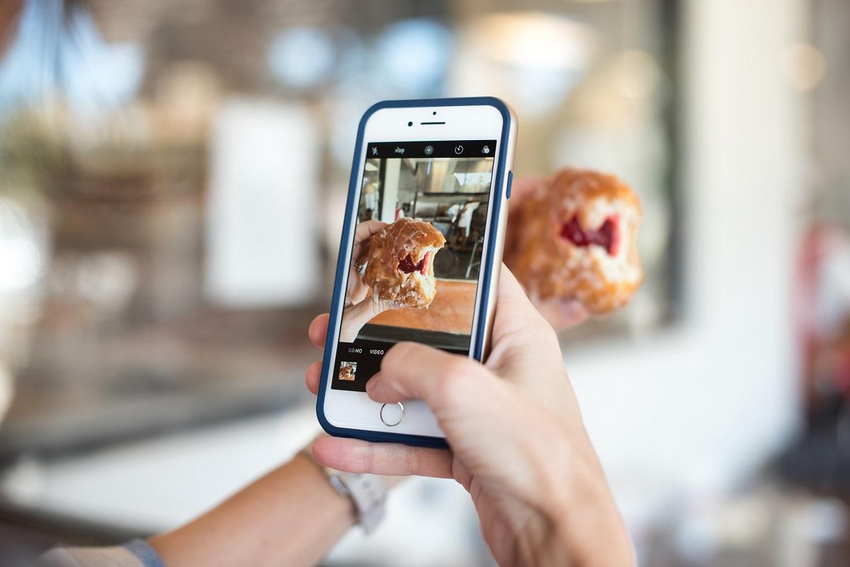 persoana care face o fotografie la mancare cu telefonul pentru pagina de Instagram