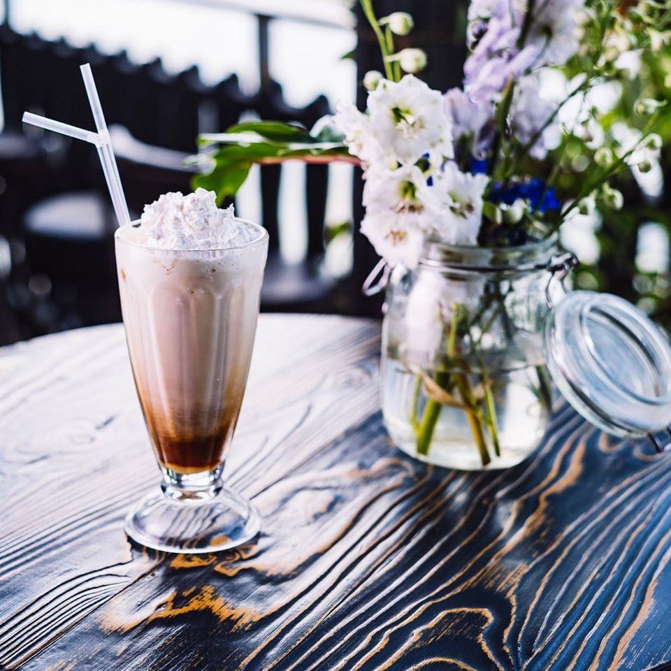 frappe bun intr-un pahar transparent, cu frisca, pe masa langa un borcan cu flori albe, la funky lounge București