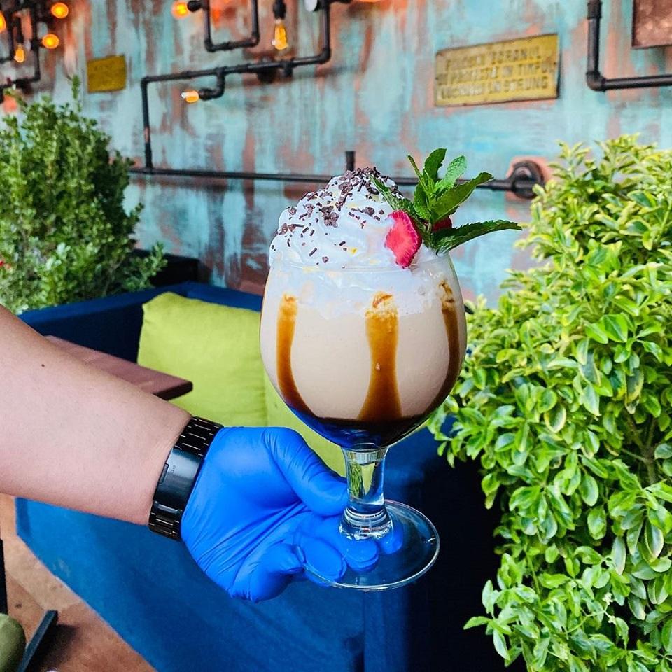 prim plan cu un pahar de frappe cu frisca si cireasa, servit de o mana cu manusa albastra, la freddo bar & lounge București