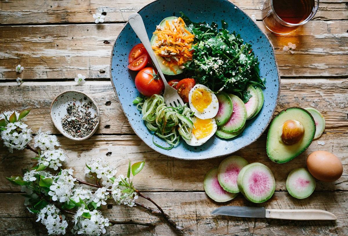 ingrediente sănătoase la salat, preparata intr-o farfurie albastra, cu ou si avocado si rosii si verdeataă