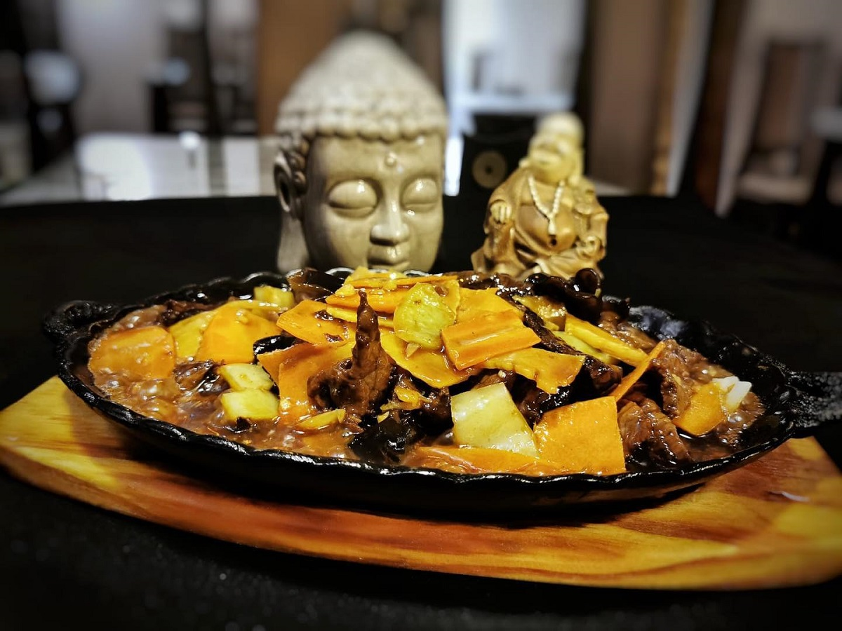 plita incinsa cu bucati de carne si legume galbene, iar in fundal o statueta chinezeasca, la restaurant harbin bucurești