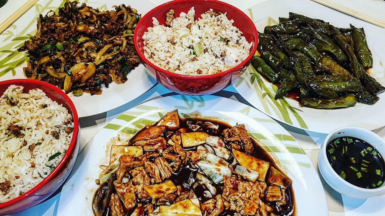 mai multe farfurii si boluri de mancare cu mancare chinezeasca cu paste, orez, carne, vita de vie si legume la restaurant templul soarelui București