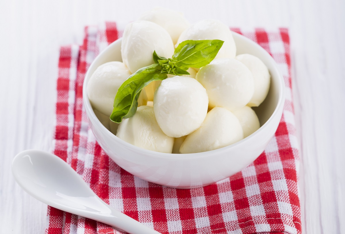 bile multe si mici de mozzarella intr-un bol alb, pe un servet cu patrare rosii, langa o lingura
