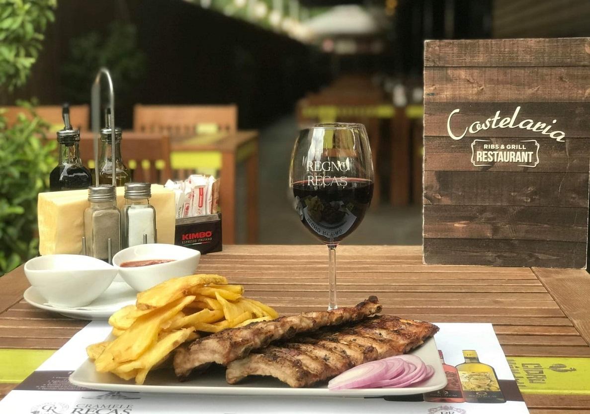 o portie de coaste la gratas cu cartofi prajiti si inele de ceapa, si un pahar de vin rosu, la Costelaria București