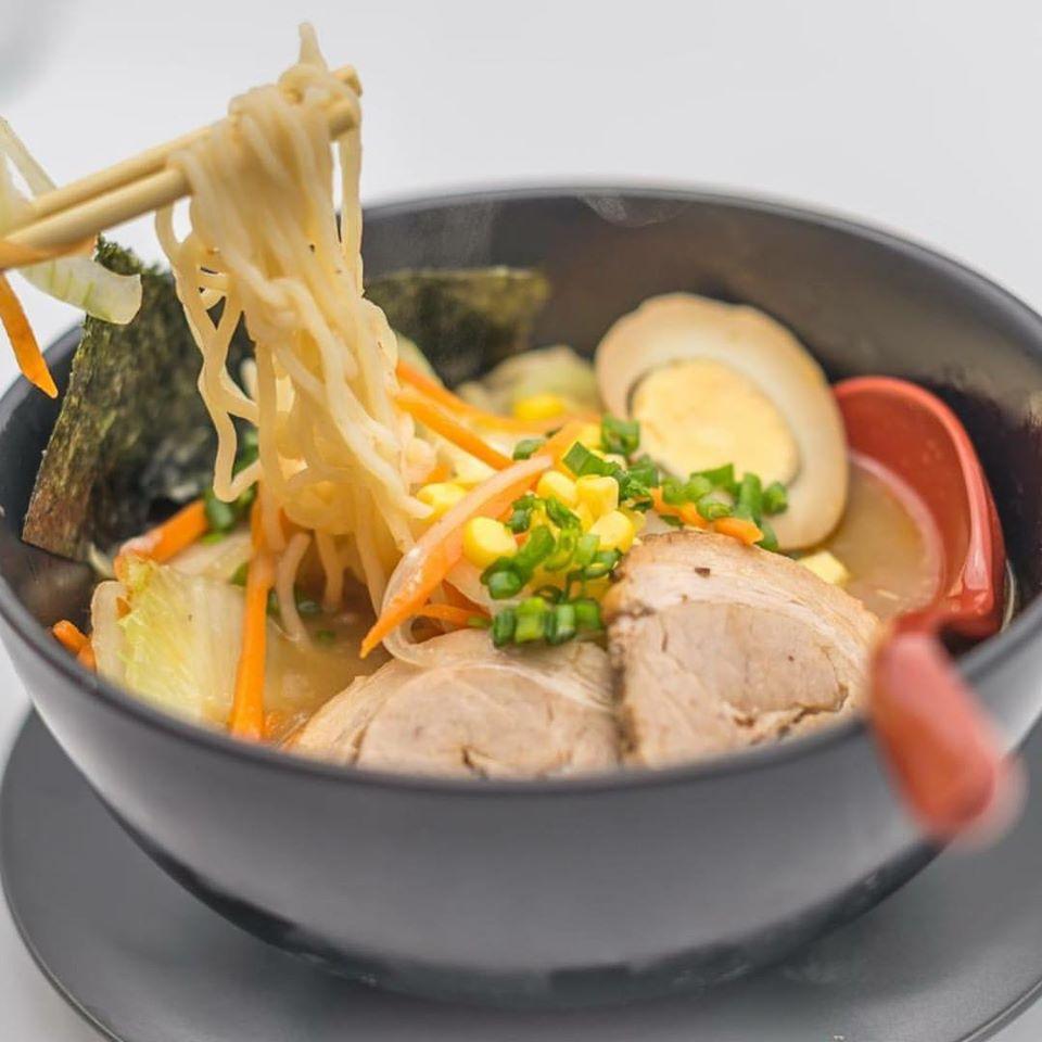 supa ramen in bol negru, cu taitei, ou si carne, si o pereche de bete japoneze langa, la Kanpai Bistro București