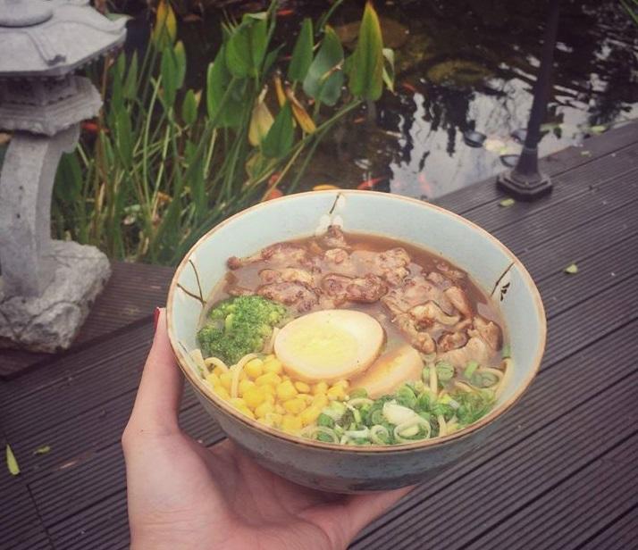 o farfurie plina cu ramen tinuta in mana de cineva, cu proumb si ou fiert, carne si verdeata, la sushi garden