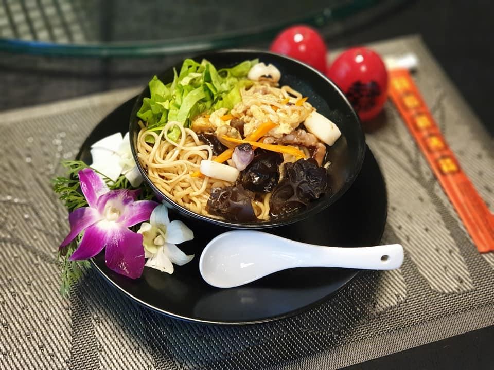 farfurie neagra pe care se afla o orhidee si un bol cu mancare chinezeasca cu taitei, carne si verdeata, si o lingura alba la restaurant zen garden bucurești