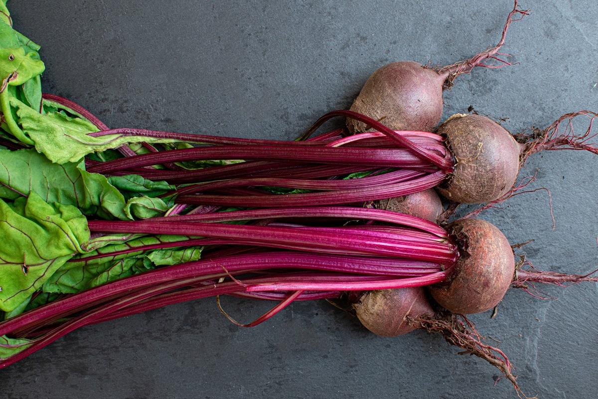 3 fire de sfeclă roșie, pe fundal negru, ca ingrediente sănătoase la salată