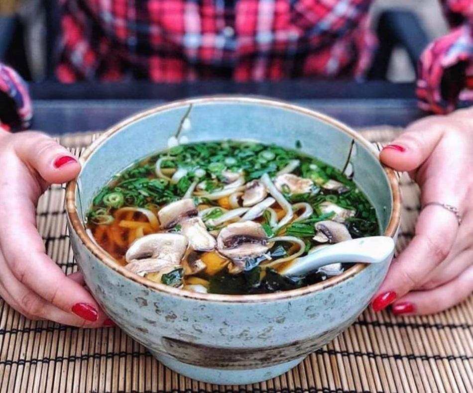 prim plan cu bol albastru cu supa ramen, tinut intre doua palme de o fata, la zen sushi București