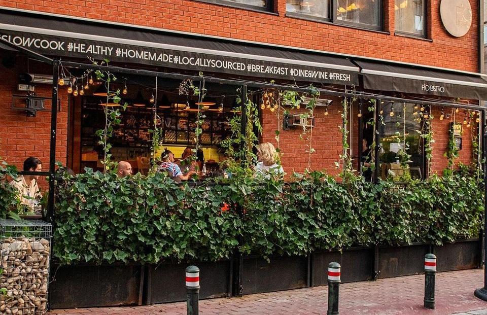 terasa de la pio bistro, imprejmuita cu ghivece cu verdeata, si cladirea restaurantului, cu caramida rosie