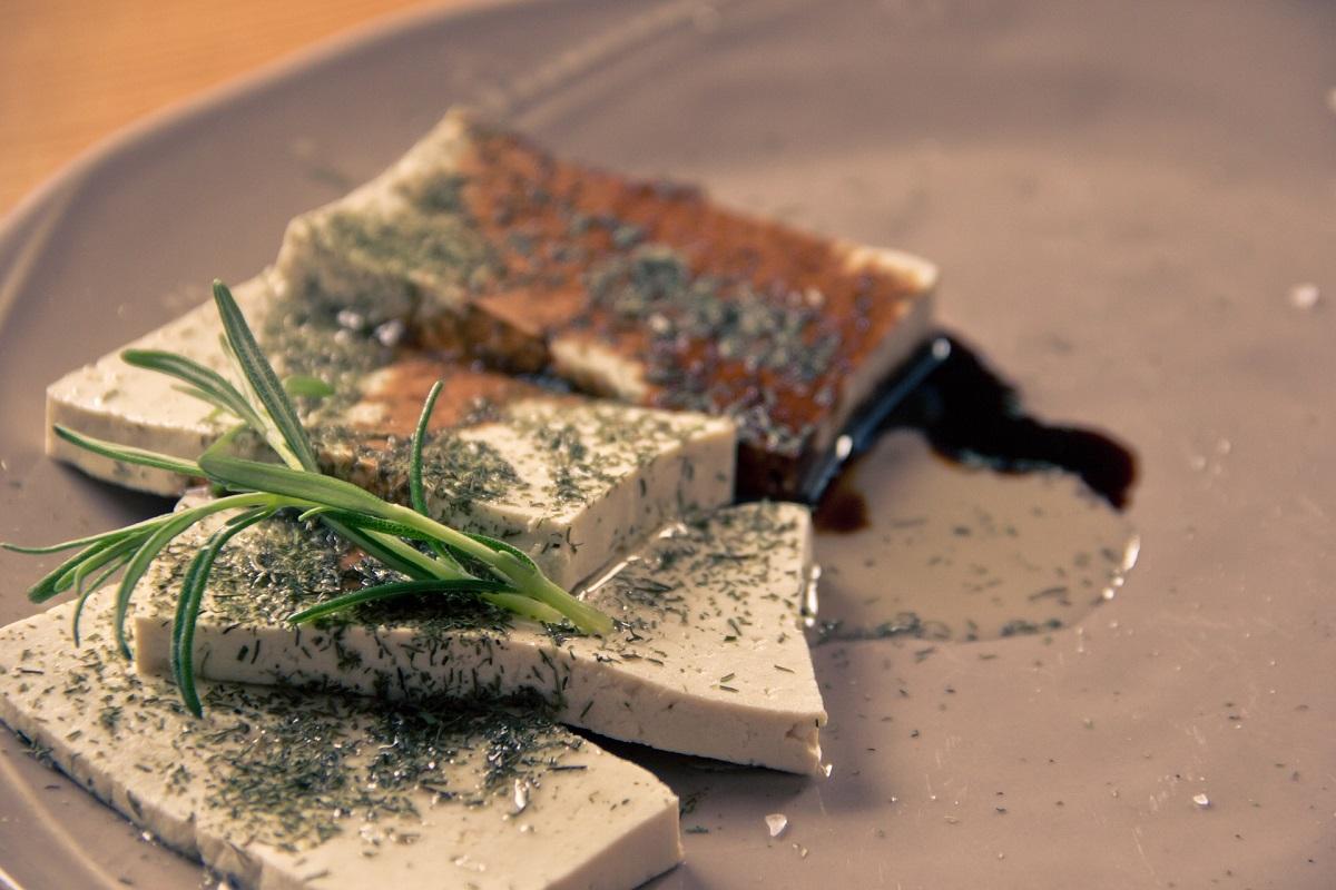 felii de tofu pe o farfurie maro, cu frunze de rozmarin si condimente presarate peste ele