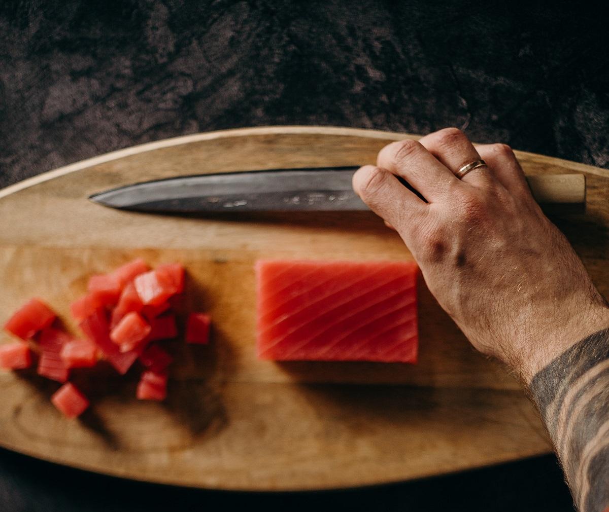 bucati de ton taiate marunt, cu o mana care tine un cutit langa, pe un tocator maro, ca ingrediente sănătoase la salată