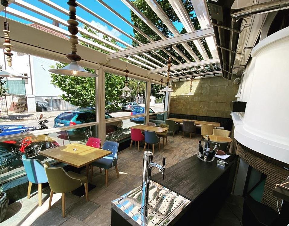terasa uptown restaurant, cu mese de lemn si scaune colorate si acoperis tip pergolă