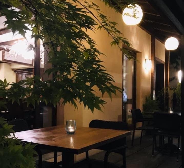 terasa yuki japonese home garden cu mese de doua persoane amplasate in curte, si lumini rotunde, in stil japonez