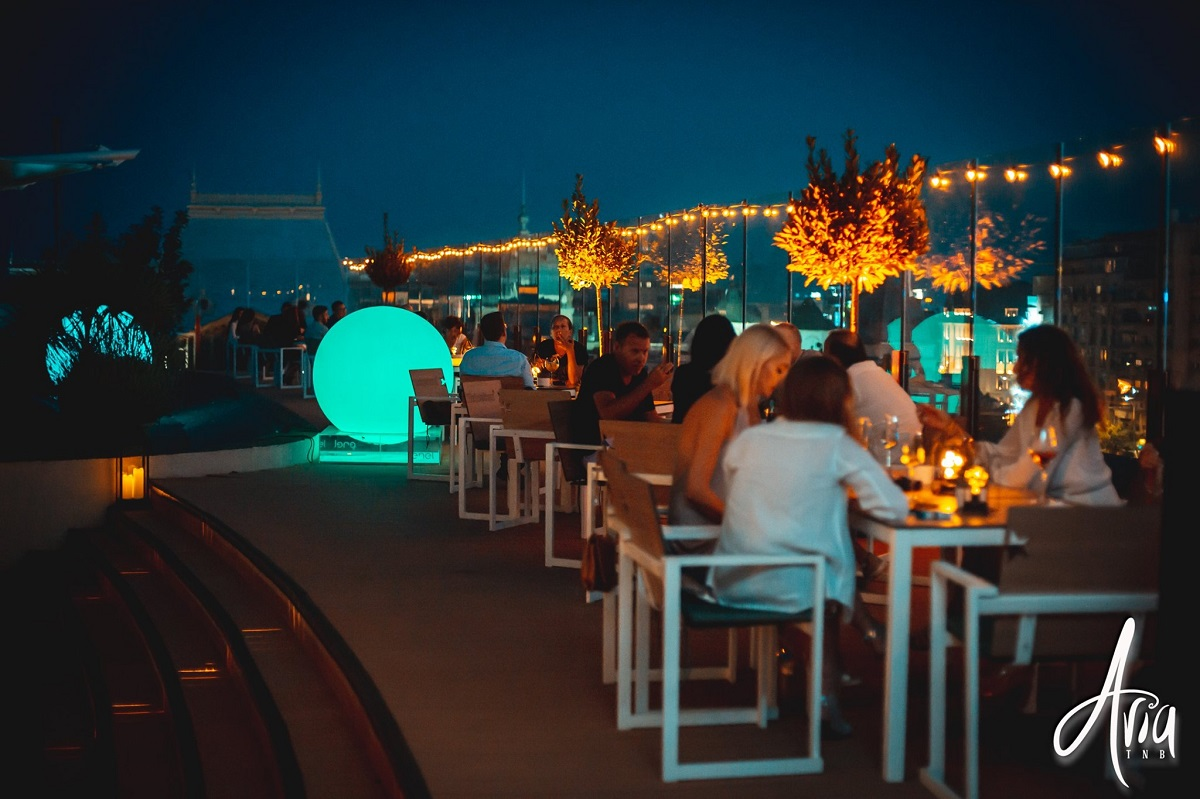 noaptea pe terasa la restaurant aria tnb, cu oameni la masa, beculete decoratieve si plante decorative luminate, restaurant la care sa te serbezi de Sf. Maria