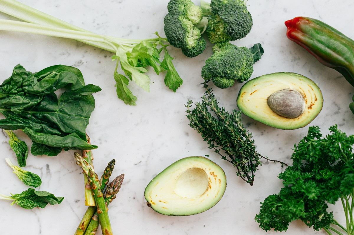 avocado taiat pe jumate, broccoli, sparanghel, cimbru verde, salata pe fundal gri