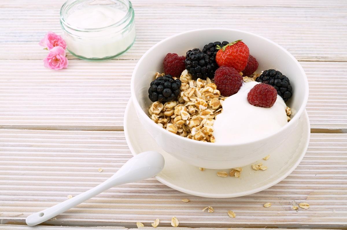 bol alb rotund cu cereale, iaurt si fructe de padure, cu o lingurita sprijinita de farfurie