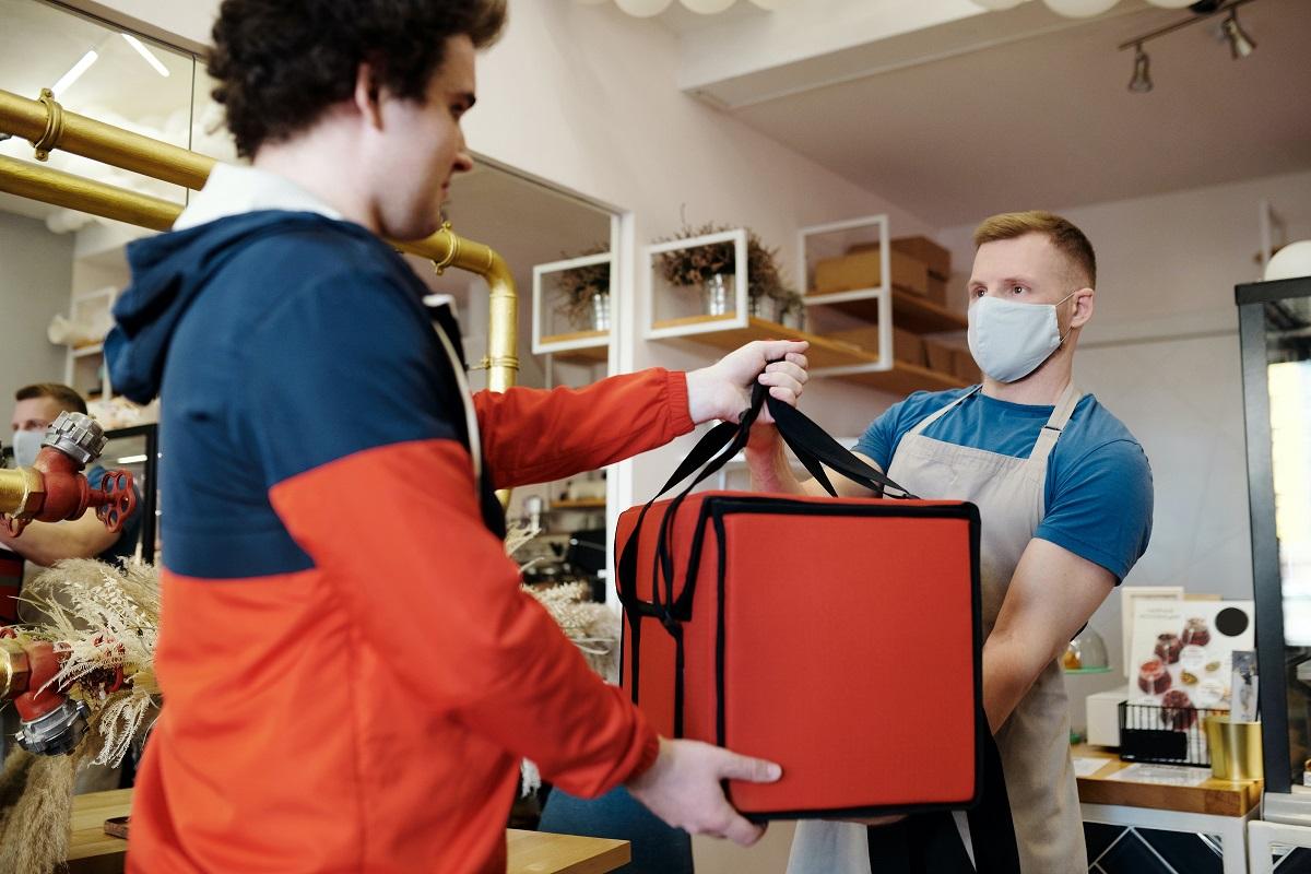 doi barbati in restaurant, unul dandu-i celuilalt c geanta de livrari cu mancare, purtand masca, imagine sugestiva pentru bune practici in restaurant pentru livrari in pandemia de coronavirus