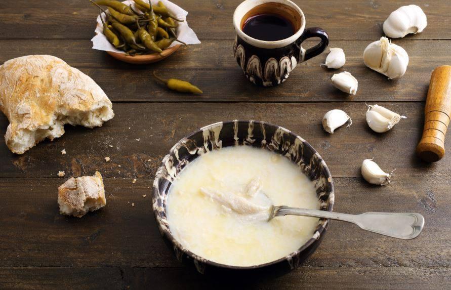 bol traditional romanesc cu ciorba de burta si o lingura in ciorba, pe o masa de lemn, cu usturoi, paine si o ceasca de tuica langa, la hanu lui manuc