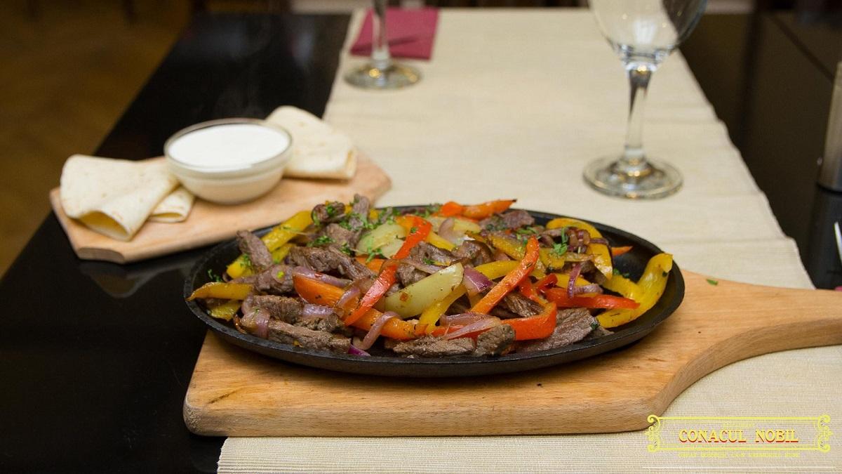 Fajitas la restaurant Conacul Nobil Pache, servita in tigaie, cu felii de carne de vita, ardei si ceapa, si sos de branza langa