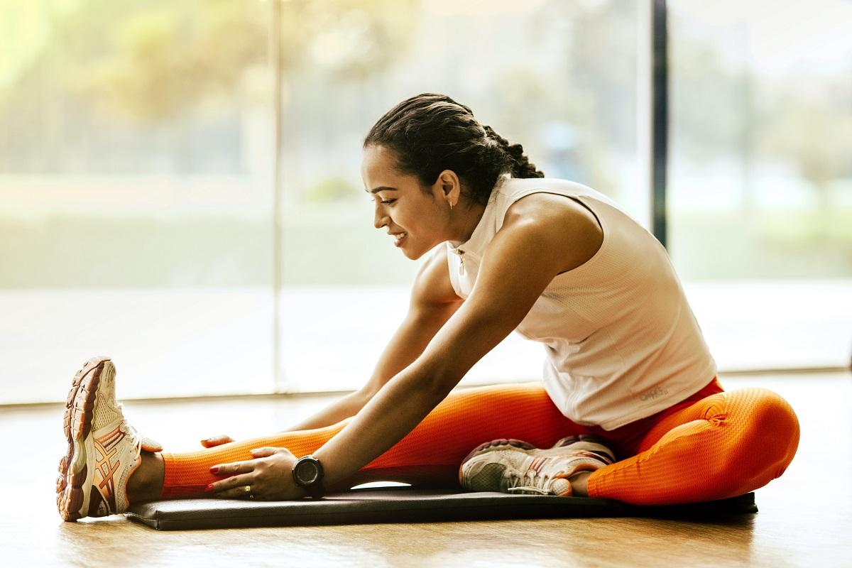 femeie imbracata sport, asezata pe podea cu piciorul intins, facand exercitii fizice