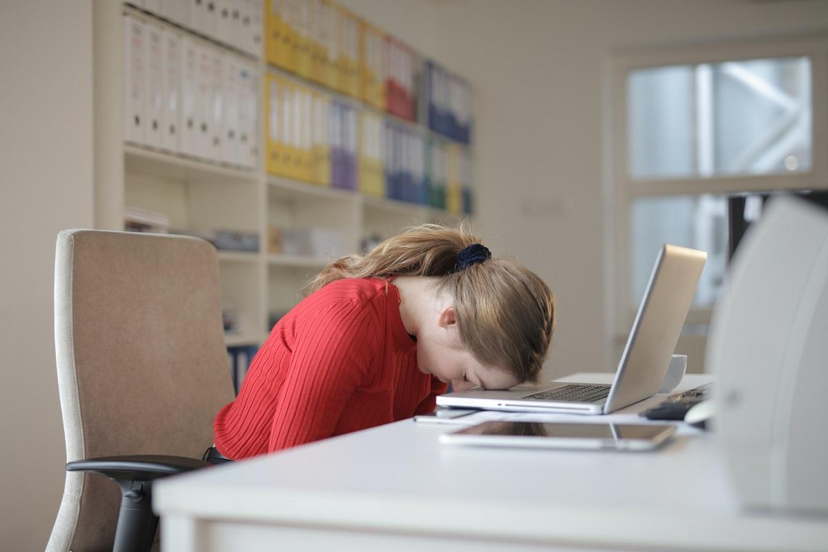 femeie stand la birou cu capul pe tastatura, ca exemplu pentru cum te molesesti daca mananci carbohidrați