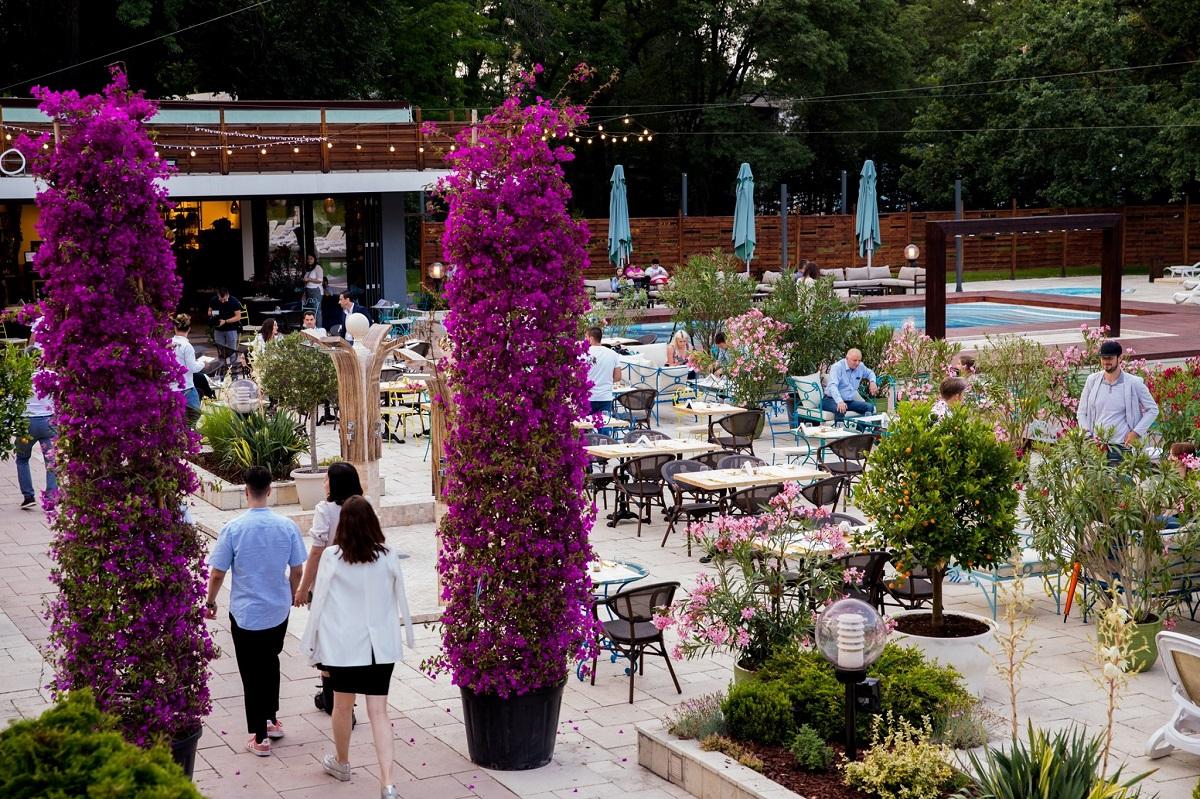 terasa de la Flavours in the garden, cu piscina in fundal, mese si arbusti mov, decorativi, restaurant la care sa te serbezi de Sf. MAria
