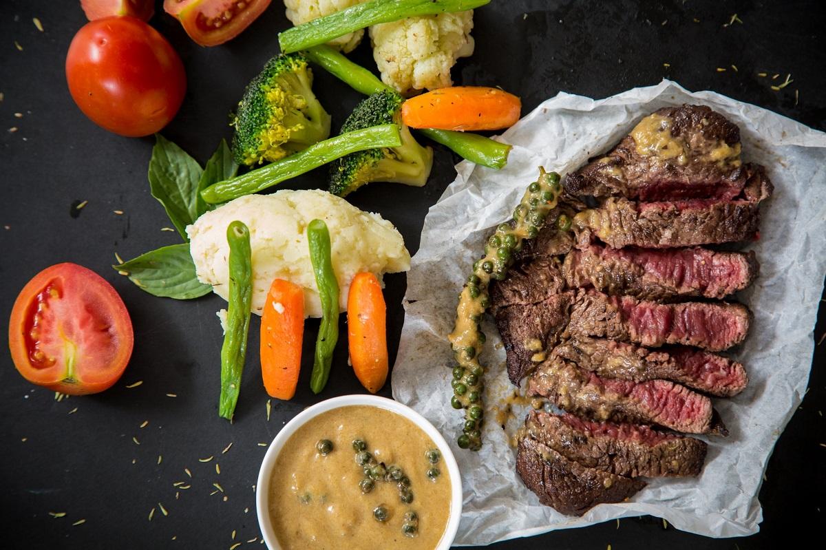 friptura de vita feliata, cu sos de mustar, asezata ăe fundal negru cu sparanghel, conopida si morcovi pe langa