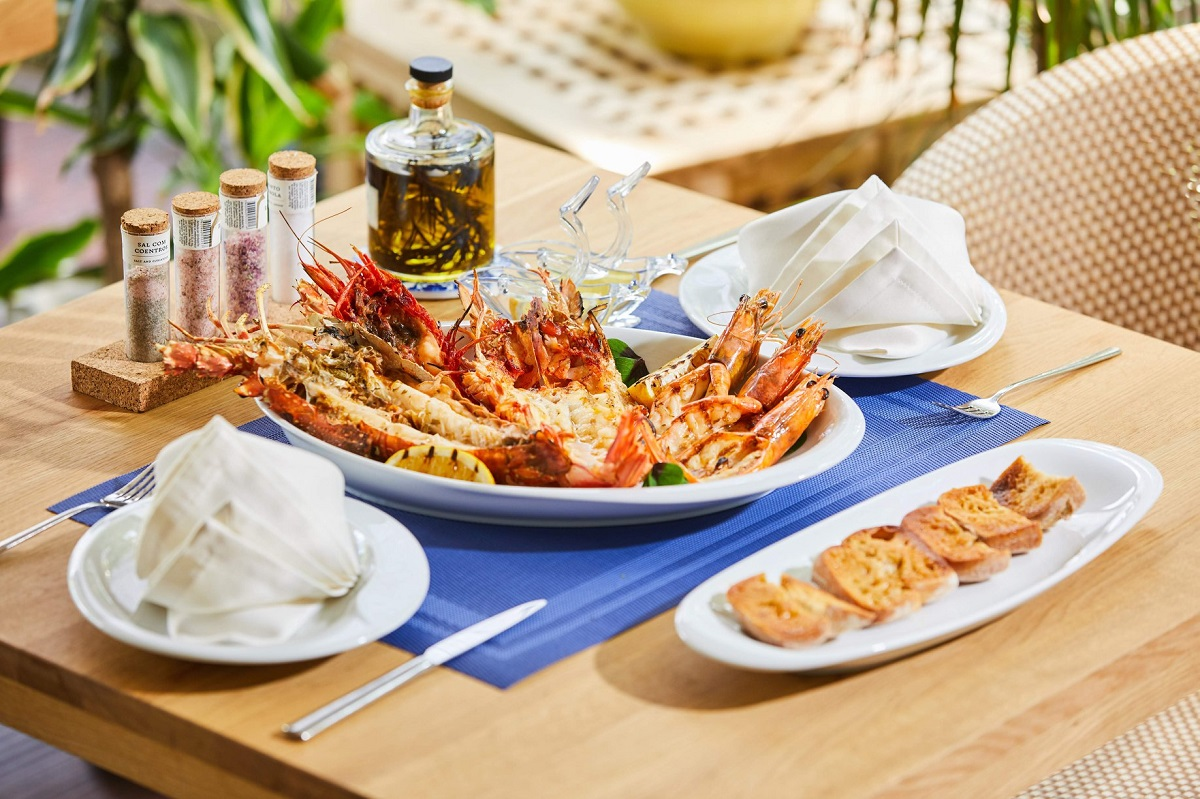 platou cu fructe de mare creveti, pe stergar albastru, pe masa de lemn, la restaurant dancing lobster terasă bucurești