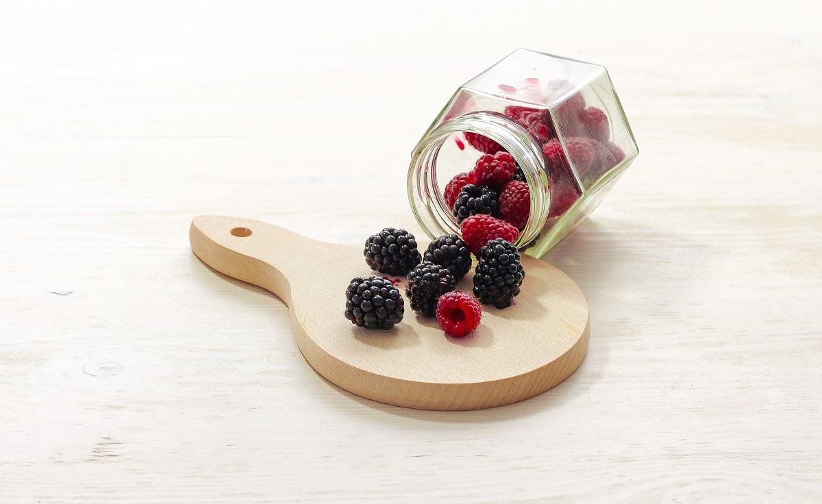 fructe de padure varsate dintr-un borcan de sticla pe un tocator de lemn