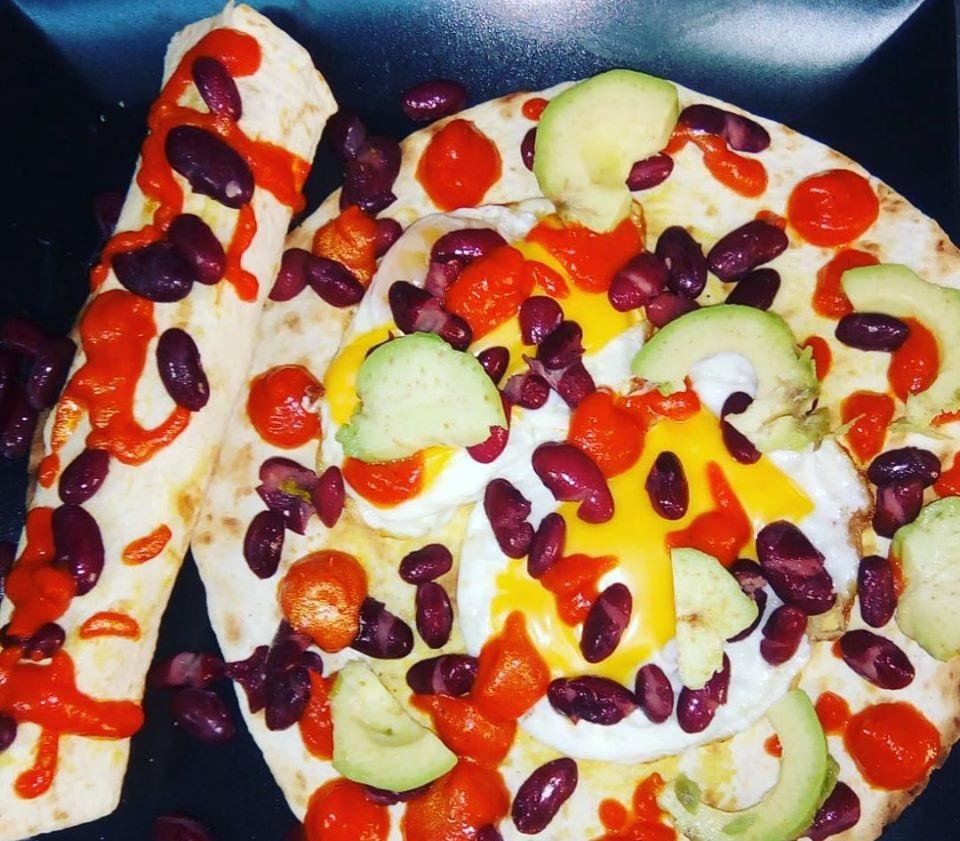 Huevos Rancheros de la Flip Flop Bistroteca, oua prajite pe o lipie de tortilla, cu avocado, fasole si alte legume si sos de branza