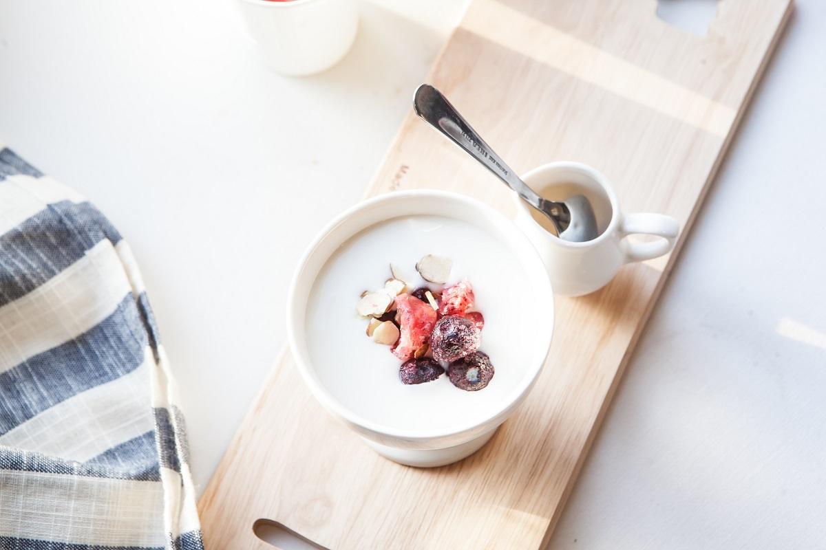 pahar cu iaurt fotografiat de sus, cu fructe si cereale si un bol cu miere langa