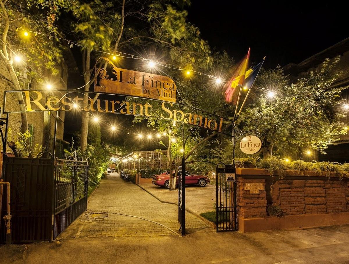 poarta de intrare in restaurant la finca by alioli, fotografiata noaptea, cu copaci in curte si beculete decorative
