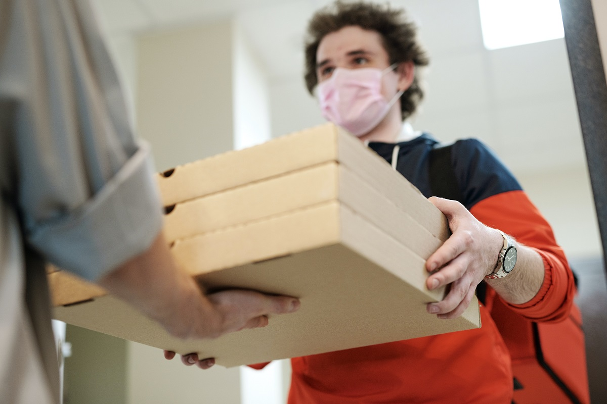 barbat care livreaza cutii cu pizza, purtand masca