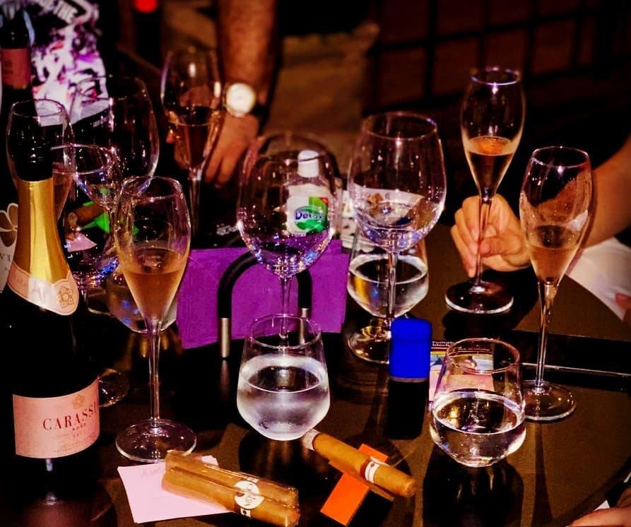 masa plina cu pahare si sticle de vin, pe fundal intunecat, la terasa Grapes The Wine Bar din București
