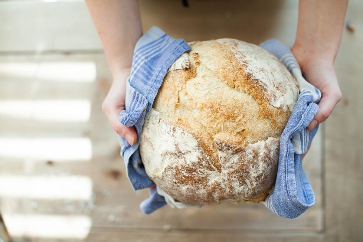 carbohidrati din paine intreaga, rotunda, tinuta intre doua maini in prosop albastru