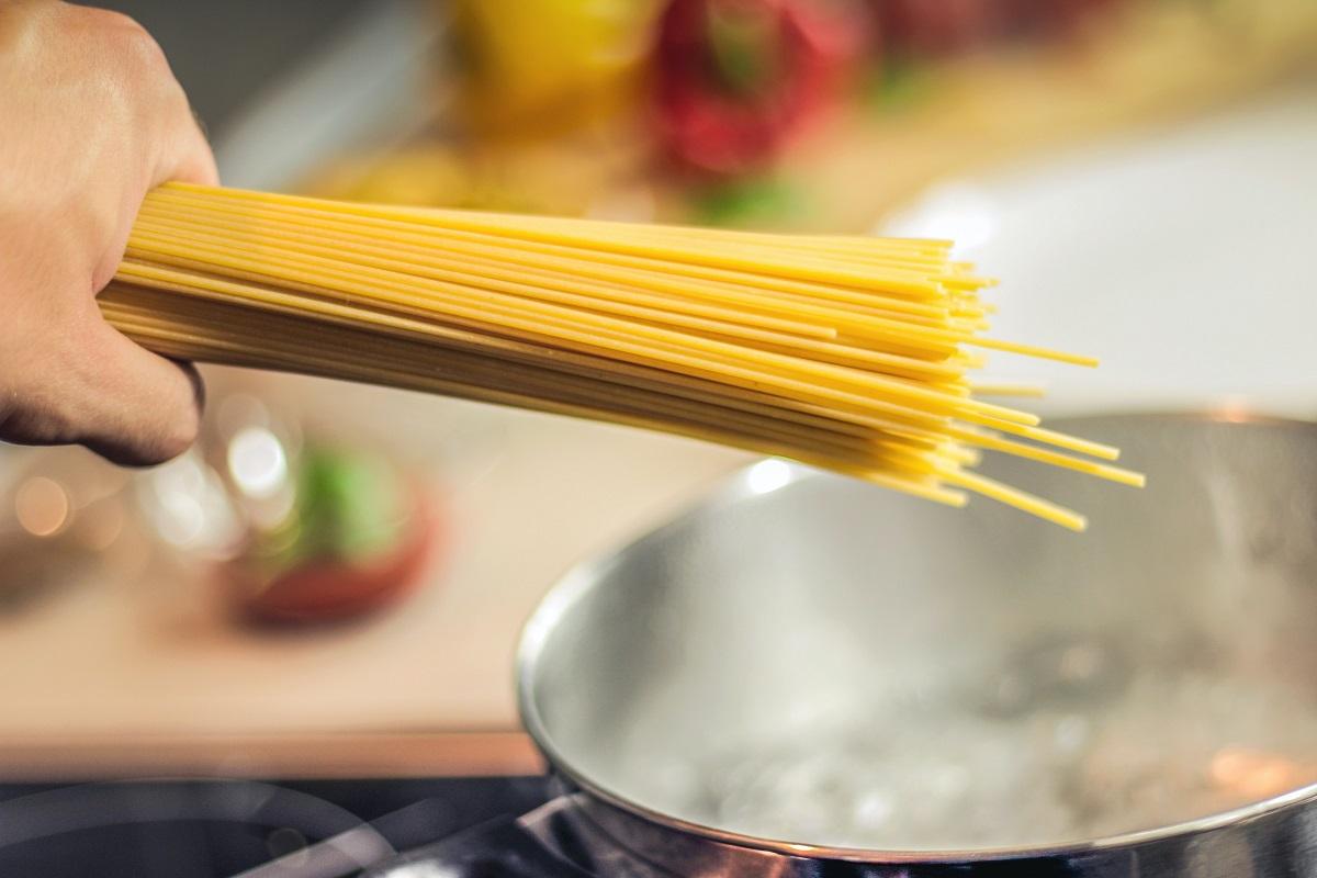 o mana de spaghete deasupra unei oale cu apa care fierbe, urmand a fi gatite