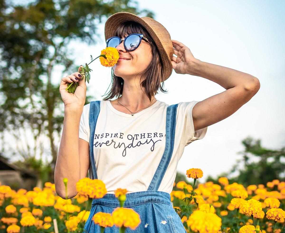 femeie in camp cu flori, mirosind o floare galbena si zambind, cu palarie si ochelari de soare, imagine reprezentativă pentru alimente care combat anxietatea in perioada de pandemie de coronavirus