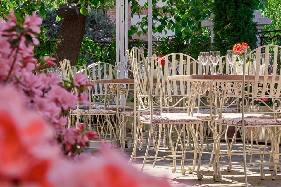 prim plan cu o floare iar in fundal mese si scaune din fier forjat la restaurant zexe zahana sofia, la care să te serbezi de Sf. Maria