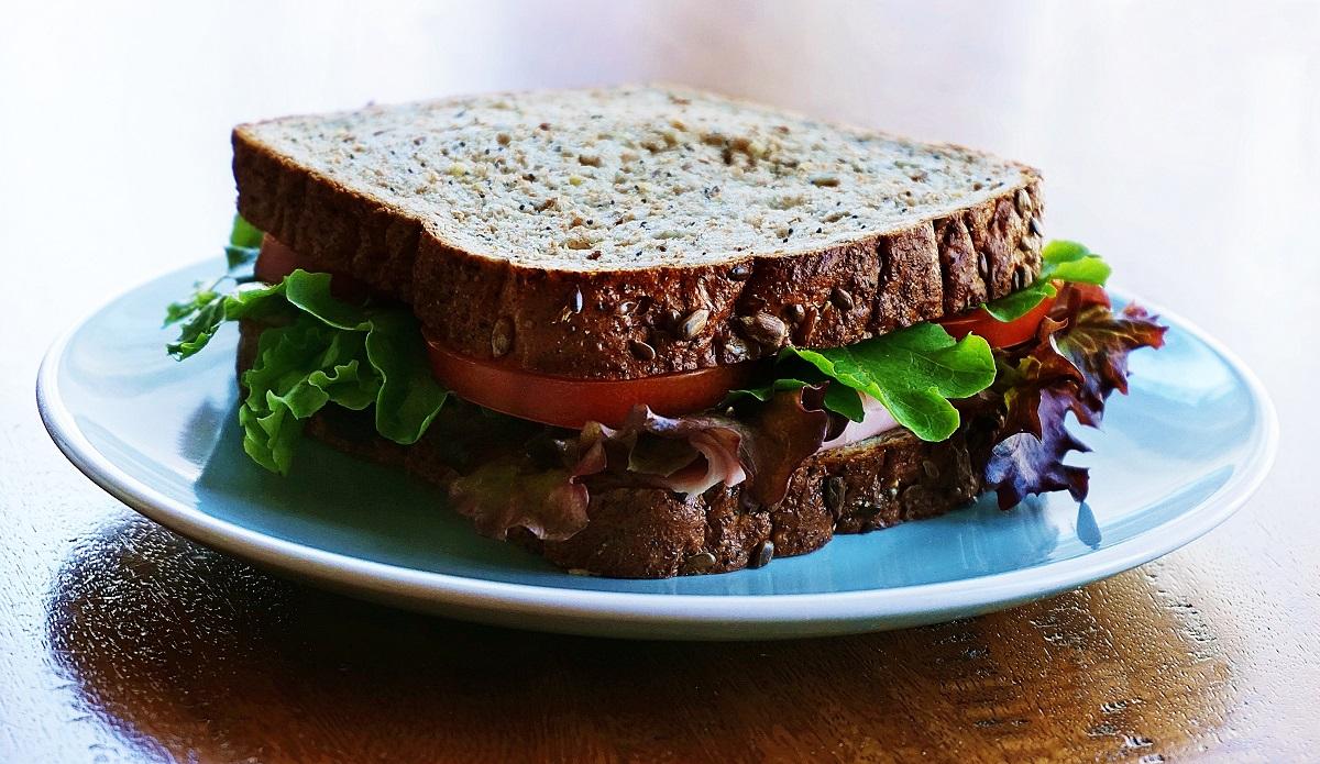 sandvici cu salata si paine integrala, pe farfurie albastra, imagine reprezentativă pentru mituri despre carbohidrați