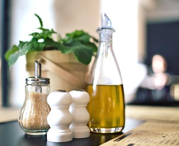 prim plan cu o zaharnita cu zahra brun, doua salnite albe si o sticla de ulei, toate langa un chiveci cu flori