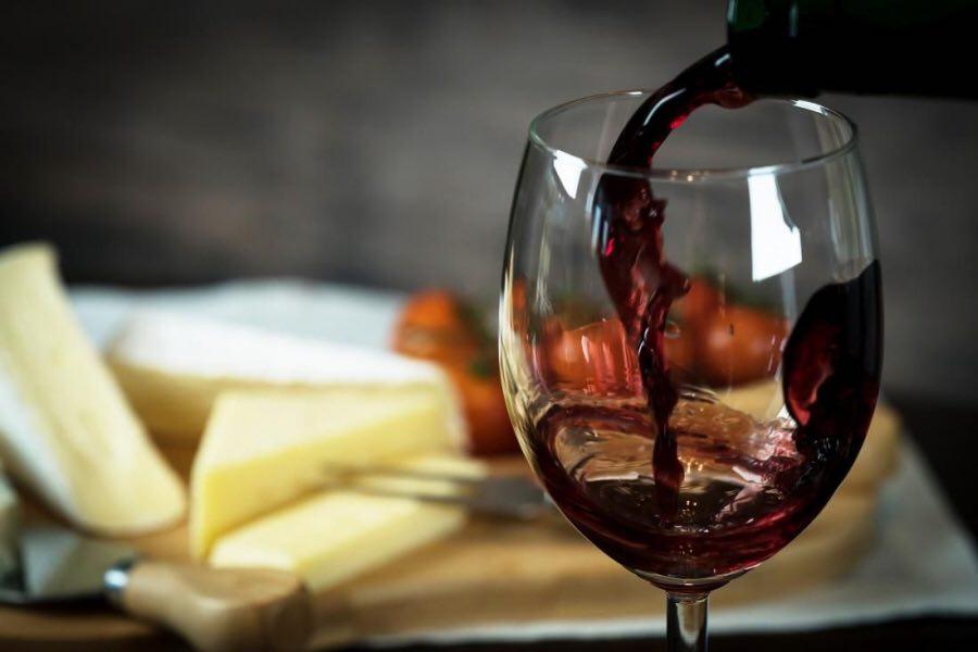 close up cu un pahar de vin in care este turant vin rosu din sticla, cu un platou de branzeturi in fundal, la terasa bruno wine bar unde bei vin bun în București