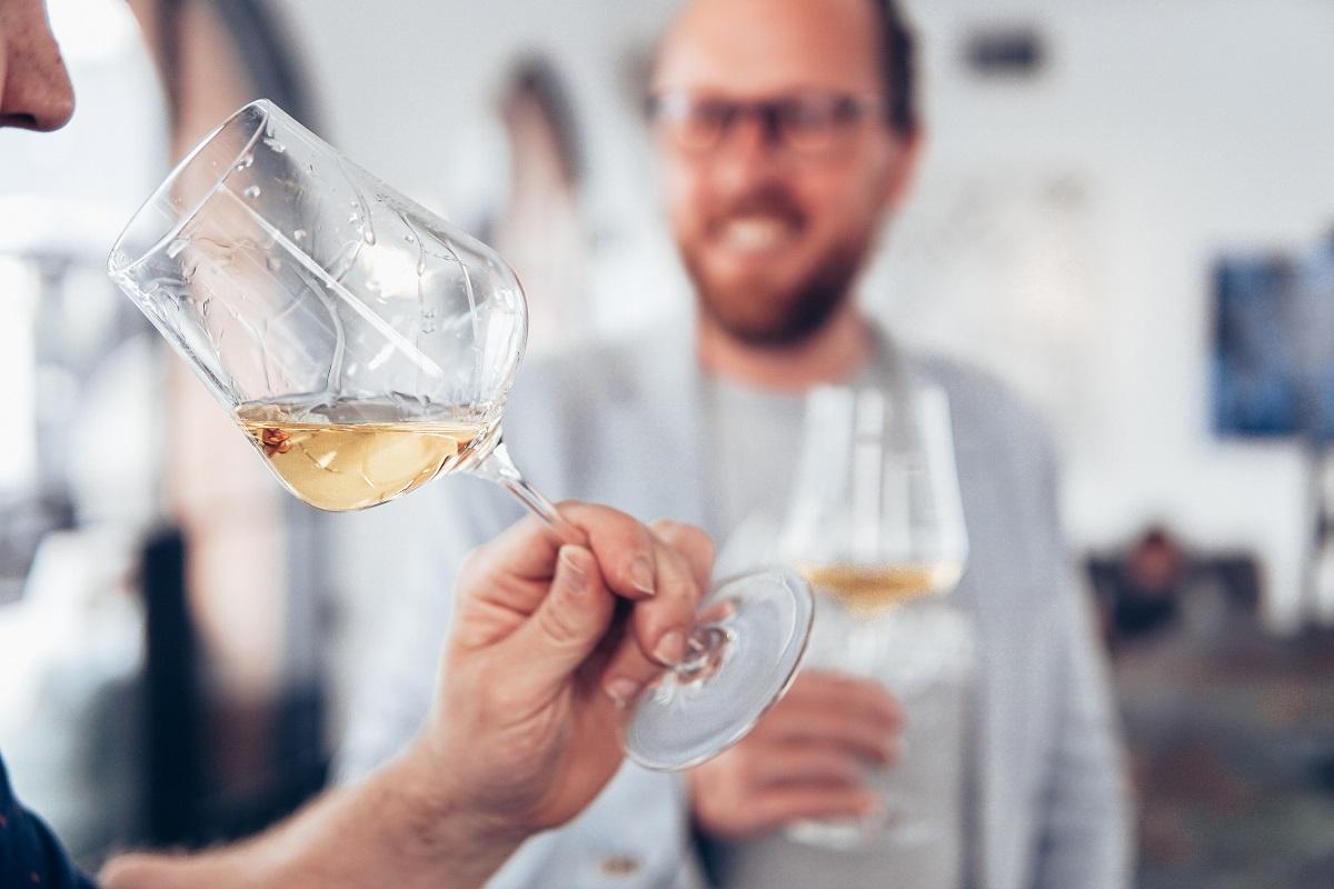 close up cu un pahar de vin tinut in mana de cineva si in fundal, blurat, un barbat, imagine reprezentativă pentru terase unde bei vin bun în București