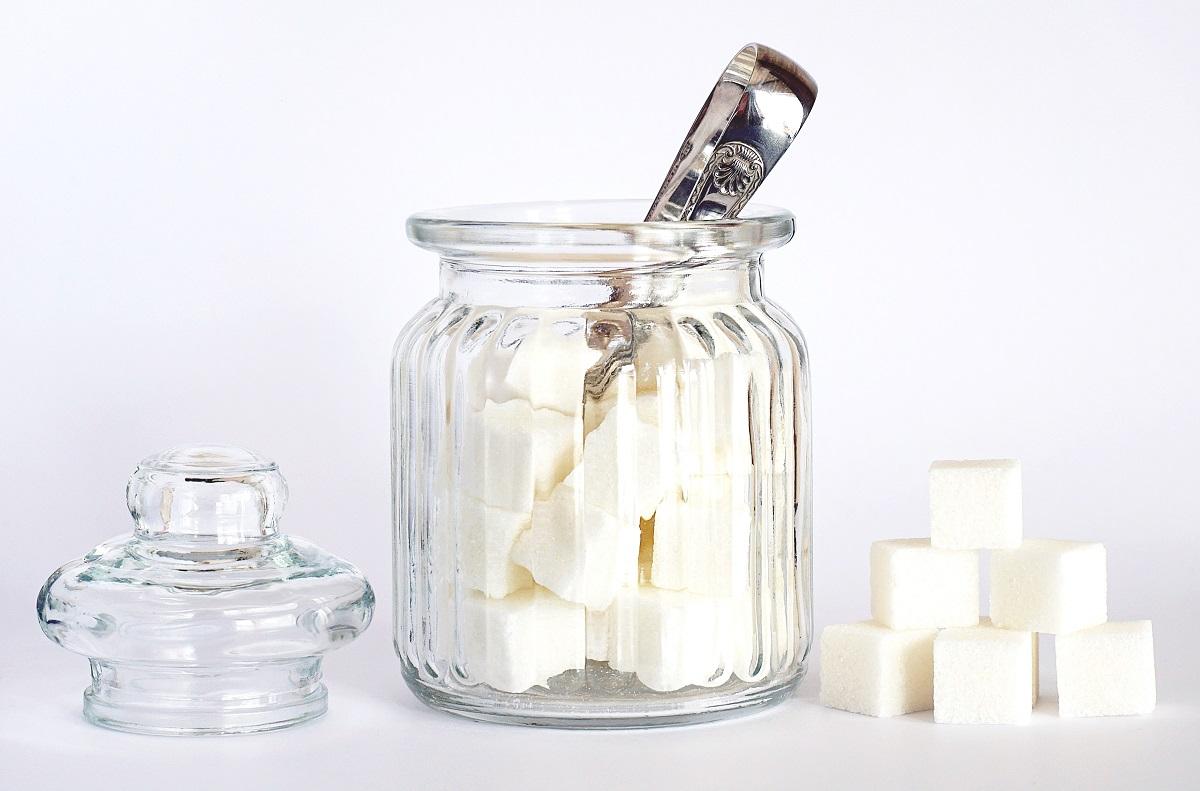 zaharnita din sticla cu cuburi de zahar in ea si langa, cu capacul desfacut si clama metalica